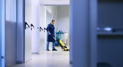 Salariée d'une entreprise de nettoyage en train de laver le sol dans des bureaux.