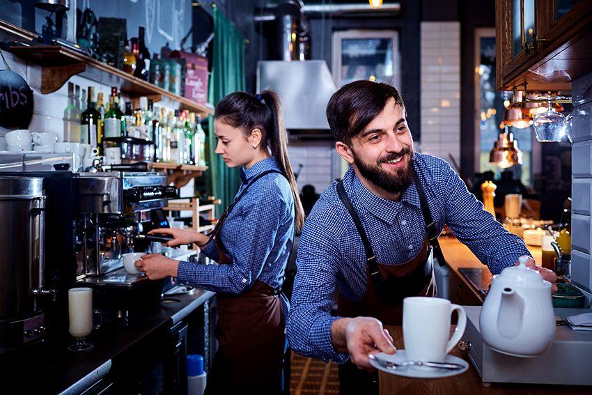 Serveuse et serveur dernière un comptoir dans un café