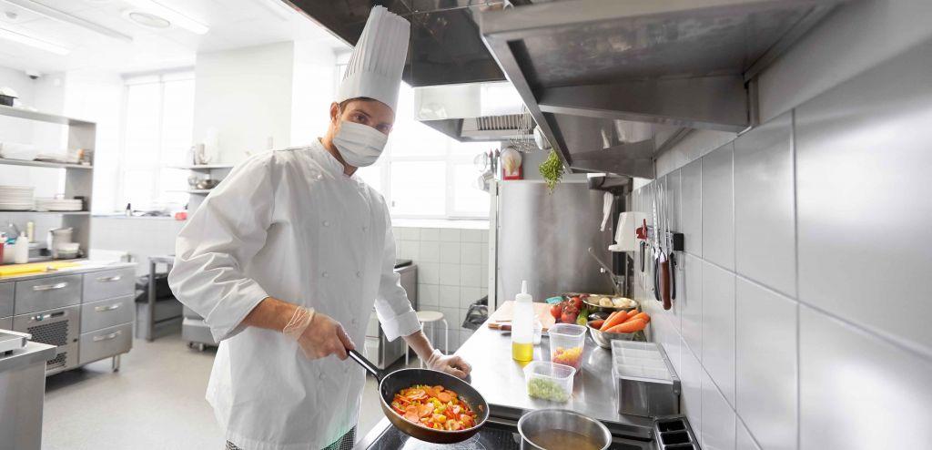 Cuisinier en cuisineportant masque et gants.