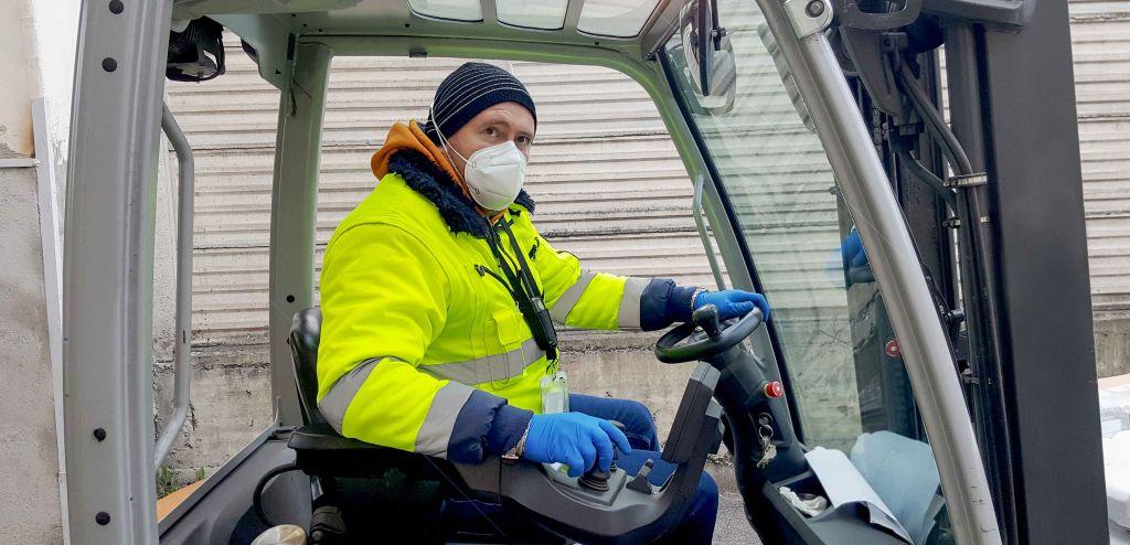 Salarié d'une entreprise de logistique portant masque et gants.